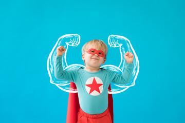 Portrait of superhero child against blue background
