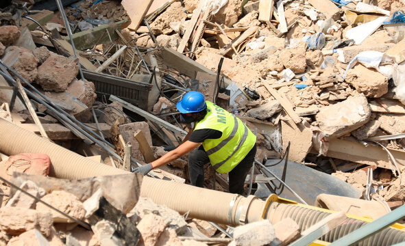 A volunteer digs through the rubble of buildings which collapsed due to the explosion at the port area, after signs of life were detected, in Gemmayze, Beirut
