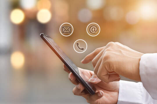 Close-up image of man hands using mobile smartphone with ( mail, phone, email ) icon. Contact us connection and social networks concept