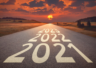 Empty road leading to the setting sun against the upcoming 2021 2022 and 2023 year