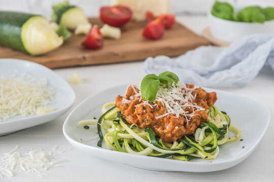 Zoodles bolognese: zucchini noodles with meat or vegan soy meat sauce and parmesan. For low carb, keto, paleo nutrition.