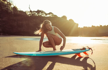 Woman preparing surfboard on beach