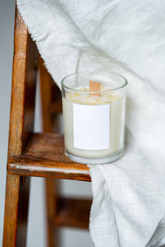 Elegant home decoration with wooden wick burning candle from soy wax. High quality photo. on a background of white linen fabric