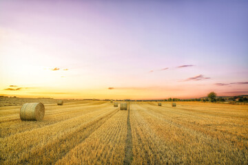 A summer hay field after harvest and large bales of hay on a warm summer evening and sunset