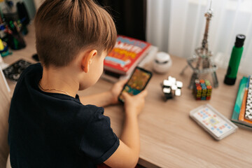 A boy holding a phone in his hands while sitting at his table at home. Addicted kid gaming. Child playing on a smartphone