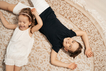 Adorable boy and girl lying on the cream carpet at home, top view. Cheerful siblings