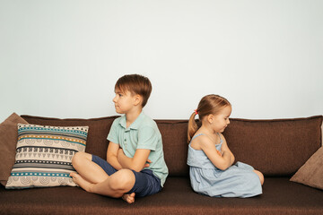 Brother and sister sit back to back on the couch upset at each other