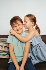 Girl whispers boy in the ear a secret. Childrens gossip