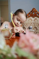 The ingenious little girl has a big dream to become a perfumer. She sits at home at a table with the bottles of perfume, smelling the aromas, making notes with her senses and ingredients