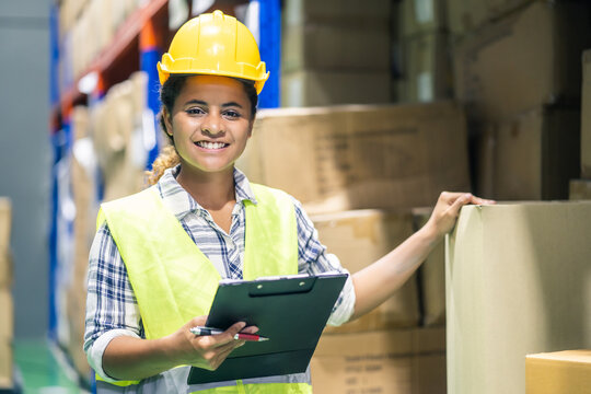 Young smiling black woman worker checking box in warehouse factory.
