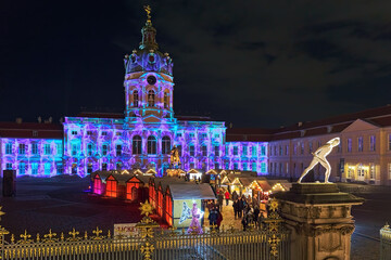 Berlin, Germany. Christmas Market in front of the famous Charlottenburg Palace in night. Facade of the Palace is illuminated with Christmas lights show.
