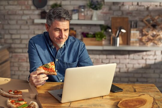 Man working from home on laptop computer, sitting at table in kitchen, eating online ordered pizza.