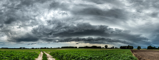 Dark stormy cloud over the fields - panorama