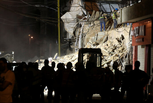 Volunteers dig through the rubble of buildings which collapsed by the explosion at the city's port area, after signs of life were detected, in Gemmayze, Beirut