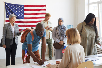 Large multi-ethnic group of people registering at polling station decorated with American flags on election day, copy space