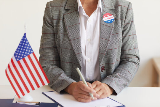 Cropped portrait of mature woman sitting at desk with American flag at polling station on election day and registering for voting