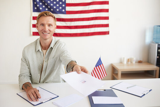 Portrait of smiling young man handing papers to people while registering voters at polling station on election day, copy space