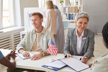 High angle portrait of multi-ethnic group of people voting at polling station decorated with American flags, copy space