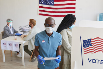 High angle portrait of young African-American voter wearing mask standing by booth and looking at...