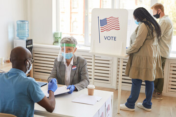 Multi-ethnic group of people wearing masks and PPE voting at polling station on post-pandemic election day, copy space
