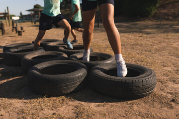 Mid section of kids walking through tires at a boot camp
