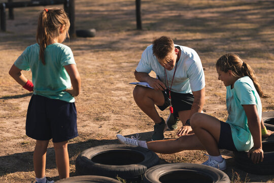 Male fitness coach looking at injured leg of a girl at a boot camp