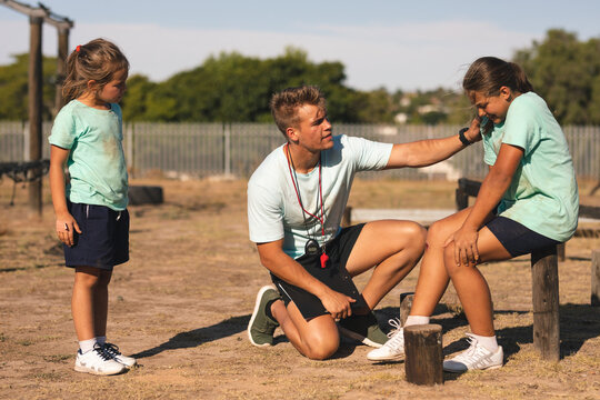 Male fitness supporting injured girl at a boot camp