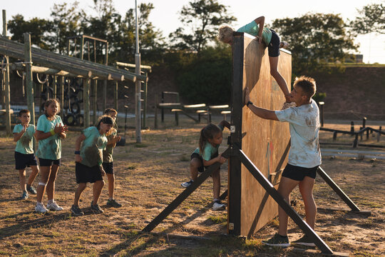 Kids climbing over a obstacle course at a boot camp