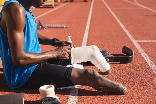 Male athlete wearing prosthetic leg on race track