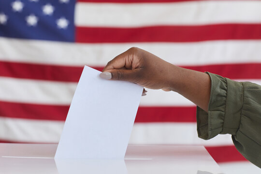Side view close up of unrecognizable African-American woman putting vote in ballot box against American flag background, copy space