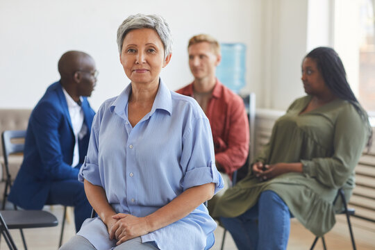 Portrait of smiling mature woman looking at camera during support group meeting with people sitting in circle, copy space