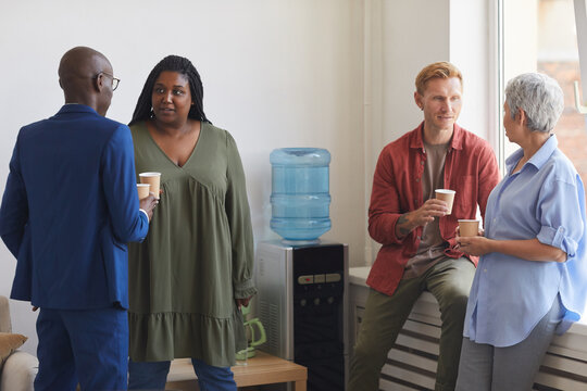 Multi-ethnic group of people drinking coffee and chatting while standing by water cooler in support meeting, copy space