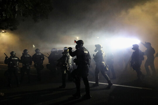 Police advance on protesters to clear a street after a Molotov cocktail was thrown on the 100th consecutive night of protests against police violence and racial inequality, in Portland, Oregon