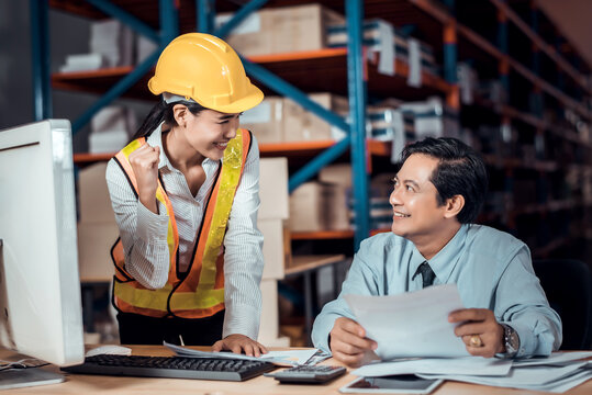 Engineer woman and businessman wearing a hardhat standing cargo at goods or merchandise warehouse and check control loading from Cargo freight ship for import and export. Teamwork successful concept.
