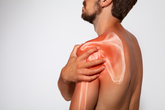 Shoulder scapula pain, man holding a hand on a painful zone