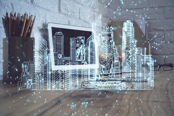 Desktop computer background in office and big town buildings hologram drawing. Double exposure. Smart city concept. Papier Peint