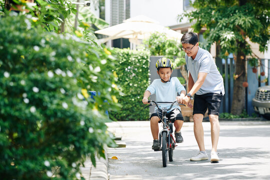 Cheerful father holding hadlebar of bicycle when his preteen son is riding for the first time