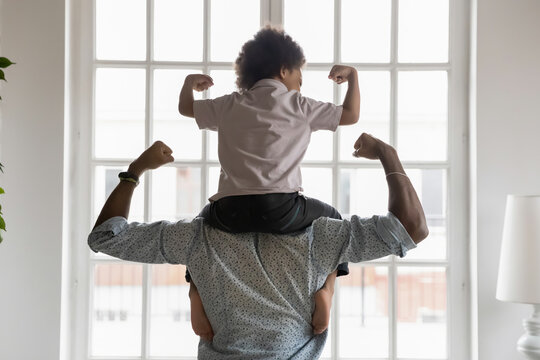 Back side view young african american father holding on shoulders little preschool funny kid son, showing biceps. Fit strong different generations family enjoying domestic activity, healthcare concept