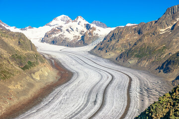 Great Aletsch Glacier, the largest glacier in the Alps and UNESCO heritage from Eggishorn viewpoint, 2869 m above sea level in Canton of Valais, Switzerland, Europe. Summer season, clear blue sky.