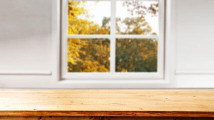 Blurred autumn window background and desk fo free space for your decoration