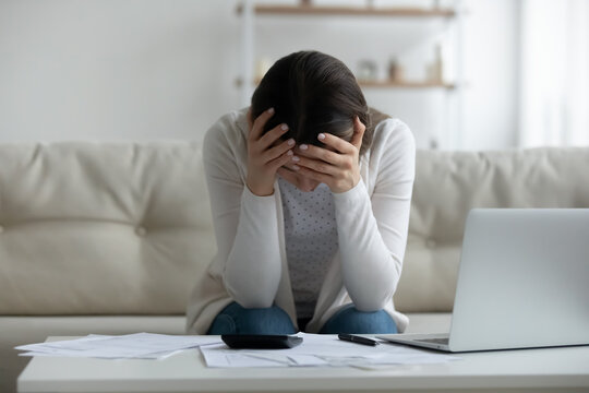 Frustrated young woman holding head in hands, feeling stressed about financial problems. Unhappy millennial girl having troubles with managing budget, termination banking letter, bankruptcy concept.