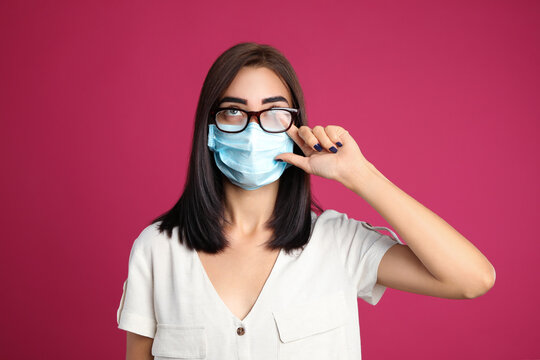 Young woman wiping foggy glasses caused by wearing disposable mask on pink background. Protective measure during coronavirus pandemic