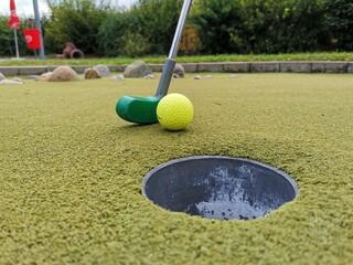 Golfschläger mit Ball beim Einlochen