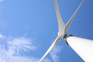 Wind turbine against beautiful blue sky, low angle view. Alternative energy source