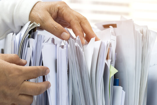 Office workers arranging stacks of lot documents report papers waiting be managed on desk in busy office. Concept of workload in business finacial paperwork information planing
