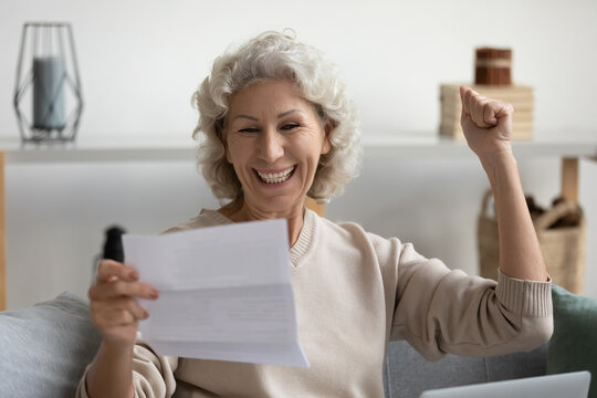 Overjoyed smiling middle aged woman reading good news in letter close up, showing yes gesture, excited happy mature female holding document, working with correspondence, sitting on couch at home