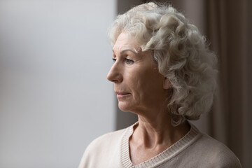 Close up upset thoughtful mature senior woman looking out window, standing at home, frustrated...