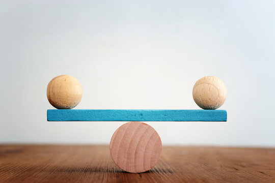 Concept of finding the right balance. Wooden balls on seesaw