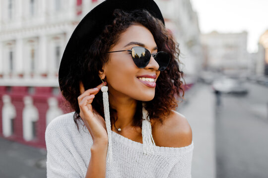 Sensual african lady in trendy  outfit enjoying good day on photoshoot. Perfect candid smile, white teeth. Black hat.