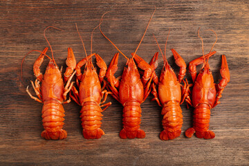 Delicious boiled crayfishes on wooden table, flat lay